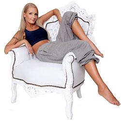 Frau in Jogginghose posiert auf Sessel